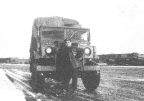 Charles Bouchard, standing next to a Royal Canadian Army Service Corps transport vehicle.