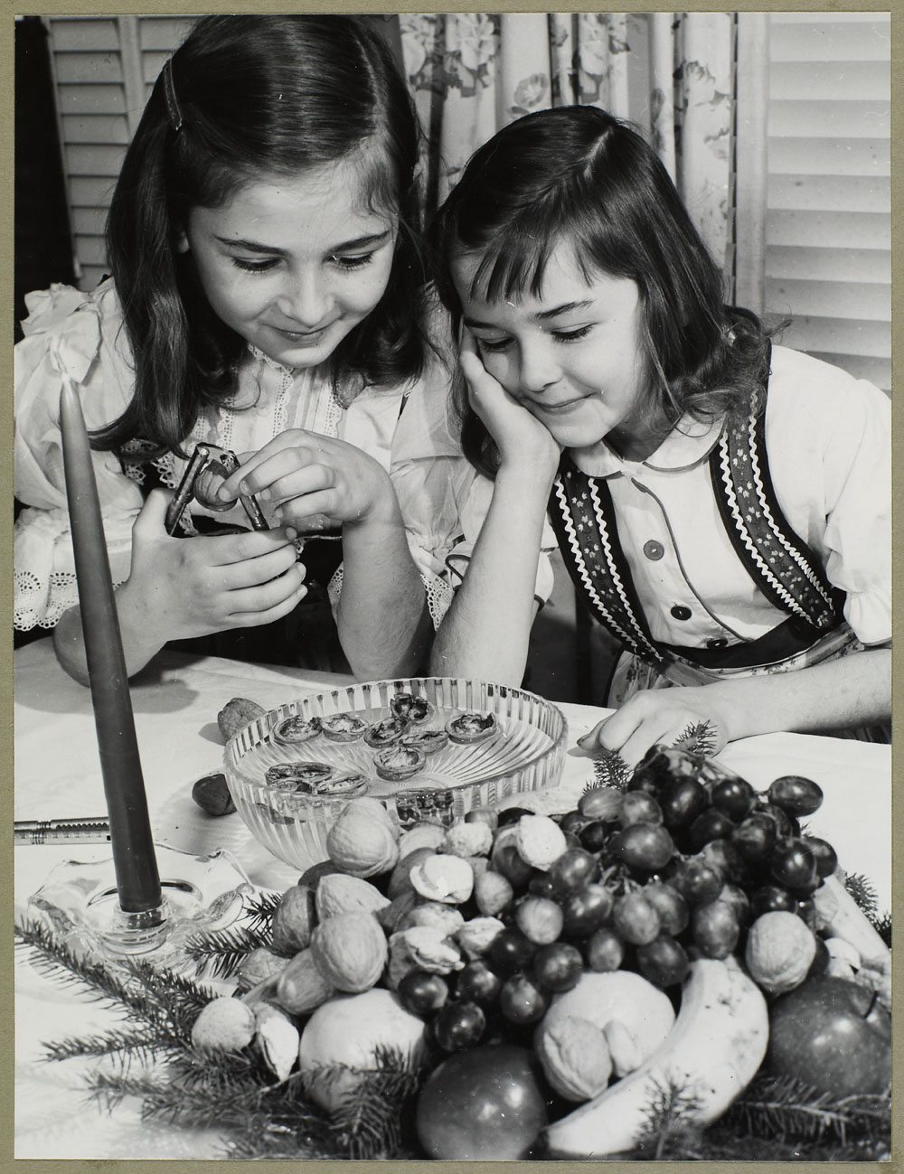 Two young Czech girls cracking walnuts at the dinner table (between 1930 and 1960)