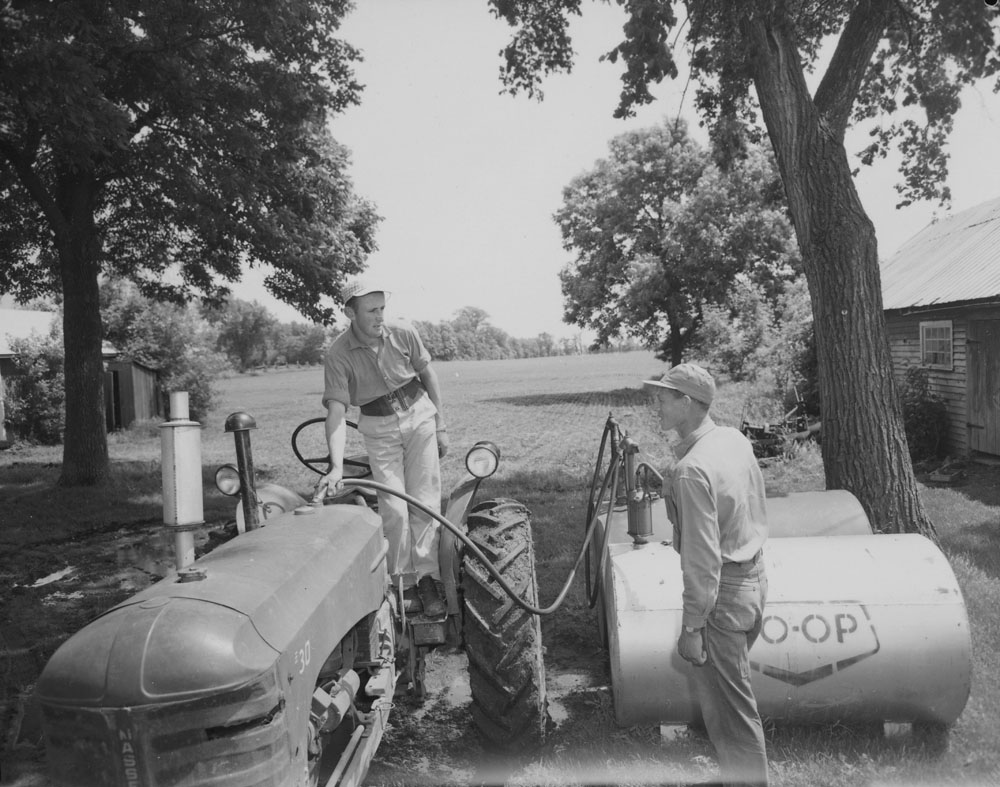 Two male Belgian workers pumping fuel into a tractor on a Canadian farm