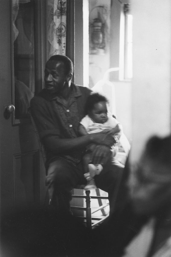 A man and baby inside a home in Africville,1965.
