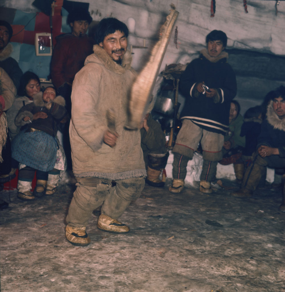 Inuk man playing a drum