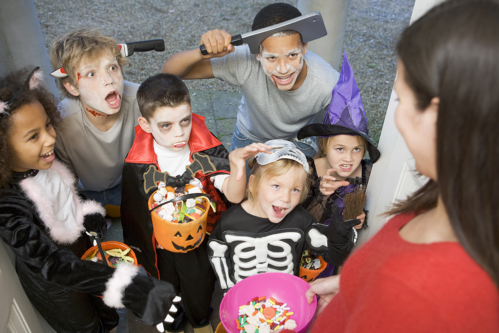 Six children in costumes trick or treat at house
