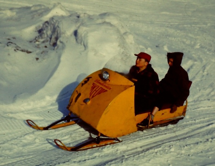 Photo of two poeple riding a Ski-Doo over snow