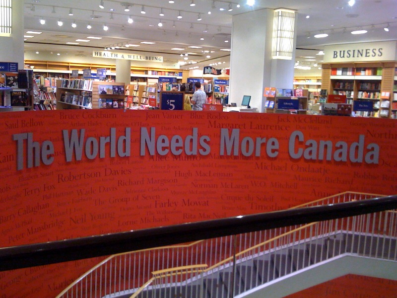 "Photograph taken inside the Indigo store at the Eaton Centre in Toronto, Ontario. The words ""The World Needs More Canada"" run along a wall displaying the names of Canadian authors."