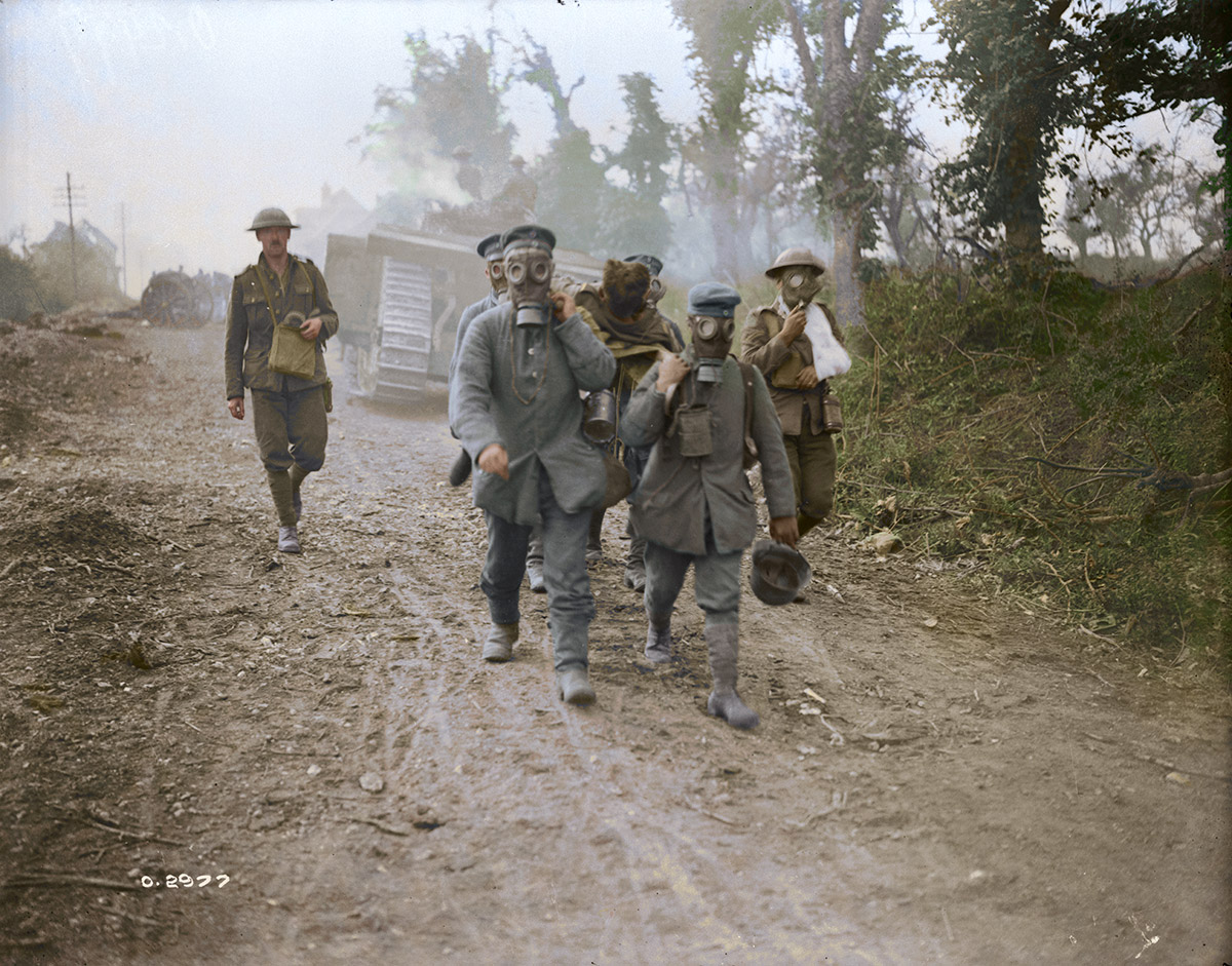 (Battle of Amiens) Tanks advancing. Prisoners bring in wounded wearing gas masks. Aug 1918.