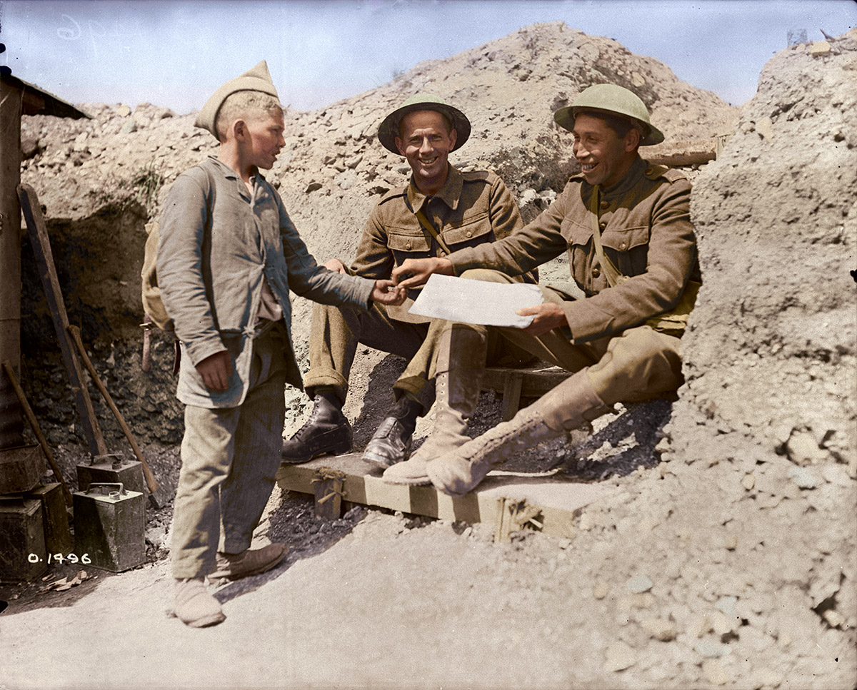 Pte. Tom Longboat the Indian long distance runner buying a paper from a little French newspaper boy. June, 1917.